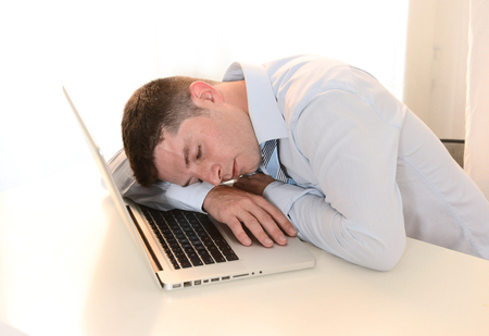 Tired Overworked Businessman sleeping over keyboard at Work  photo