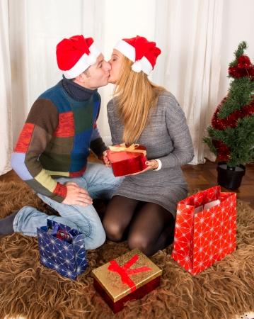 Romantic Young Happy Couple Christmas hats kissing on rug  photo