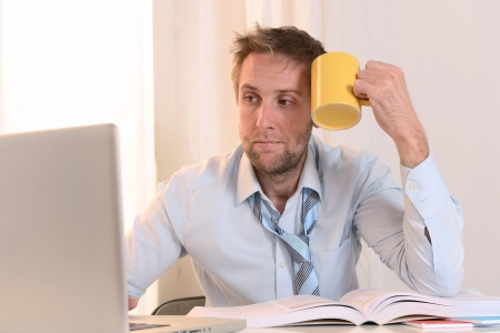 Young Student Stressed and Overwhelmed working on Laptop holding a cup of Coffee photo