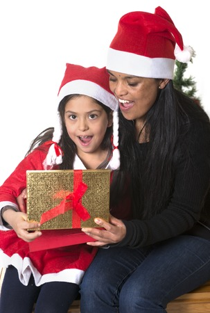 Little girl and Mother kissing and opening Christmas Present photo