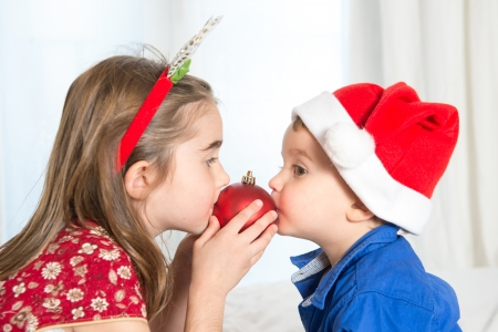 Happy Cute little kid Santa Claus hat and his beautiful sister at Christmas photo