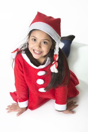 Cute Little Girl in Santa Claus costume posing happy at Christmas photo