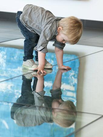 reflexion: Peque�o ni�o lindo jugando con su reflexi�n sobre el suelo Foto de archivo