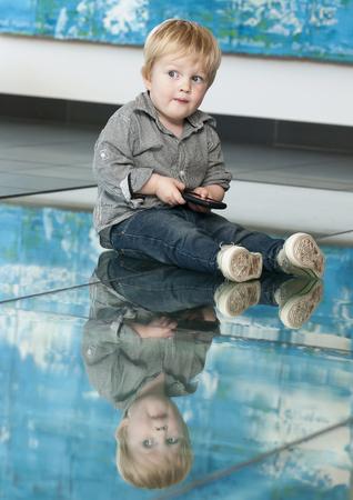reflexion: Peque�o ni�o lindo jugando con el tel�fono celular y la reflexi�n en el suelo Foto de archivo