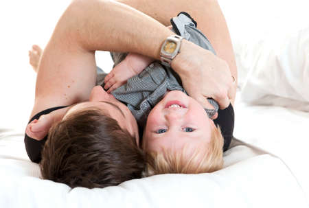 Happy Young Father and son playing on bed photo