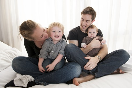 Young couple playing with baby girl and little child sitting photo