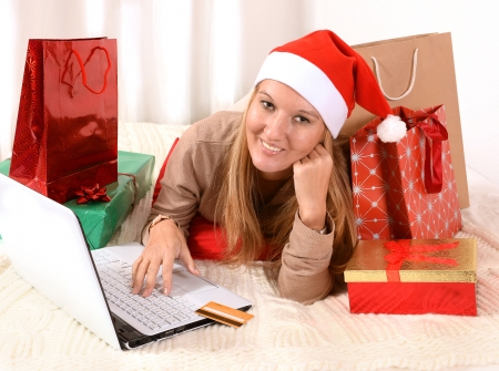 Young beautiful woman online Christmas shopping with computer and credit card   photo