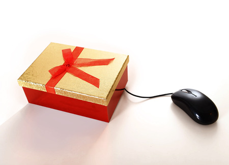 Computer Mouse conected to Christmas Present representing online shopping photo
