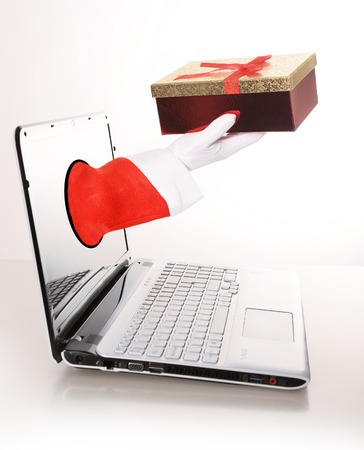 Santa Claus hand with Christmas Present out of Computer screen photo
