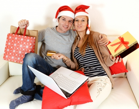 Happy young couple with laptop online shopping Christmas presents photo
