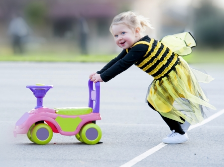 Happy blond little girl in bee costume pushing toy outdoors photo