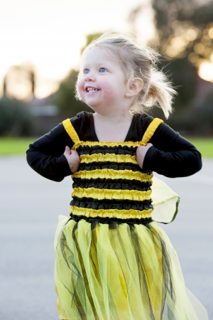Happy blond little girl in bee costume dancing and playing outdoors photo