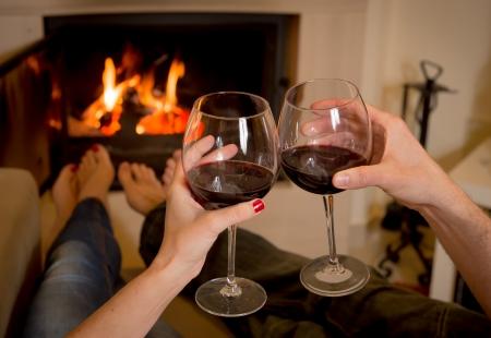 木の暖炉の前でワインを飲む若いカップルのクローズ アップ