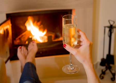 woodburner: close up of a woman relaxing in front of an open wood fire drinking Champagne Stock Photo
