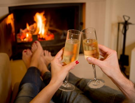 close up of young couple drinking champagne in front of a open wood fire Stock Photo - 24921816