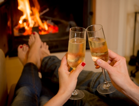 close up of young couple drinking champagne in front of a open wood fire photo