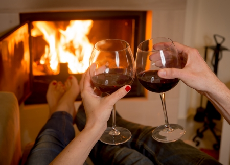dirty feet: close up of young couple drinking wine in front of an open wood fire