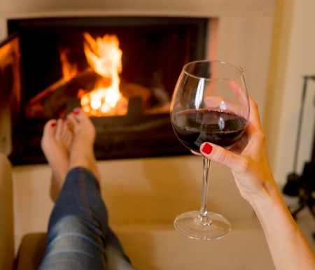 Woman holding a glass of red wine sitting in front of an open fire Stock Photo - 24921823