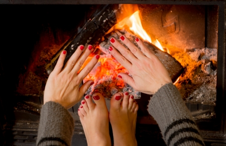 cosy: close up young woman warming her feet and hand in front of an open fire