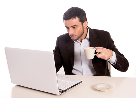 horizontal portrait of a business man concentrating on a laptop while drinking coffee  photo