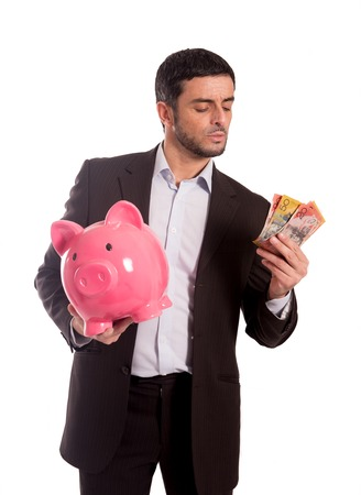 australian dollars: vertical portrait of a business man wearing a suit holding a piggy bank and AUD Australian Dollars, thinking about saving and his future