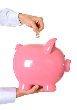 Business Man putting a coin into a huge pink piggy bank isolated on white background photo
