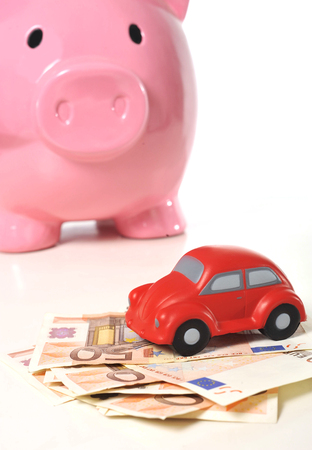 Euro banknotes and miniature car  isolated on white background representing saving to buy a new automobile photo