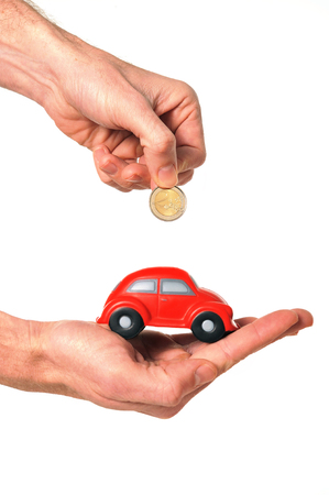 man holding coin using car miniature as piggy bank isolated on white background photo