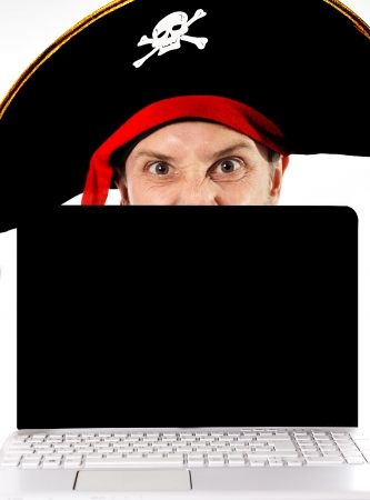 Young man in pirate costume and Computer representing illegal downloads and copyright violation isolated on white background photo