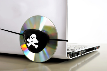 felony: Pirate Eye patch on cd or dvd disk and computer representing piracy, illegal download and copyright violation Stock Photo