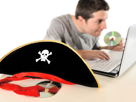 Young with Computer copying dvd and pirate hat representing illegal downloads and copyright violation isolated on white background photo