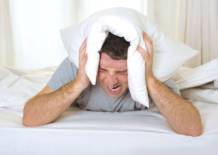 exhausted desperate young Man suffering hangover and headache with pillow on his head Stock Photo