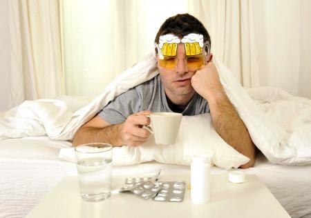 uitgeputte jonge man in bed met koffie, water en tabletten lijden kater en hoofdpijn