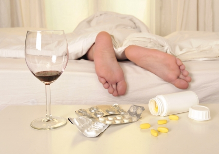 Feet on bed of sleeping man suffering hangover and headache after party with wine