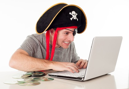 anti piracy: man dressed as a pirate on his computer downloading music and movies on a white background