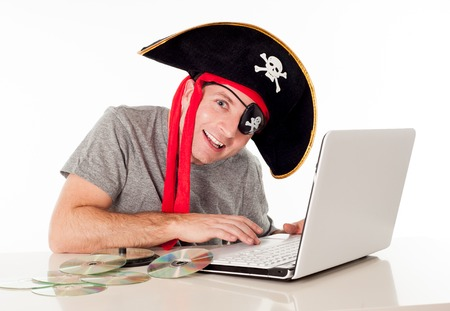 anti piracy: man dressed as a pirate with a CD in his mouth on his computer downloading music and movies on a white background