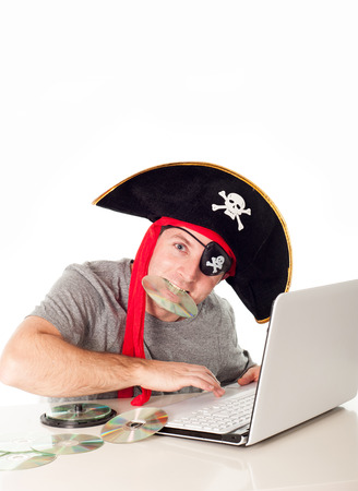 man dressed as a pirate with a CD in his mouth on his computer downloading music and movies on a white background   photo