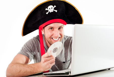 man dressed as a pirate on his computer downloading music and movies on a white background   photo