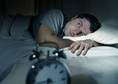 awaken: young man in bed with eyes opened suffering insomnia and sleep disorder thinking about his problem Stock Photo
