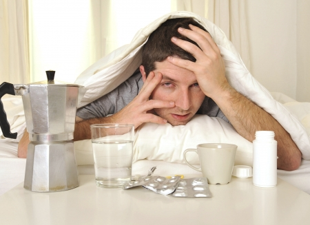 intoxication: exhausted young Man in bed with coffee, water and tablets suffering hangover and headache