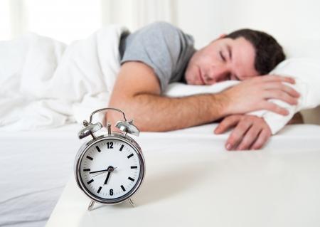 dormir: Hombre atractivo joven que duerme en cama por la mañana temprano