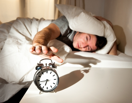 sleeping man disturbed by alarm clock early morning Imagens - 25201202