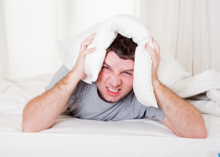 exhausted desperate young Man suffering hangover and headache with pillow on his head lazy to wake up when alarm clock rings photo