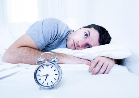 jonge man in bed met de ogen geopend lijden slapeloosheid en slaapstoornis na te denken over zijn probleem Stockfoto