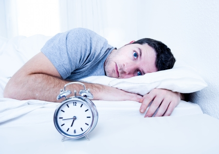 eyes opened: young man in bed with eyes opened suffering insomnia and sleep disorder thinking about his problem Stock Photo