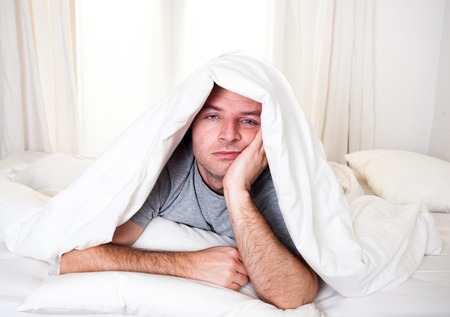 young man in bed with eyes opened suffering insomnia and sleep disorder thinking about his problem Stock Photo