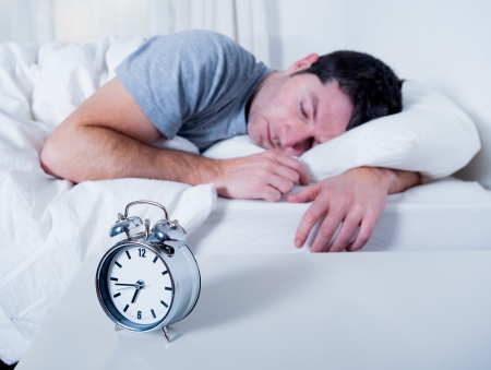 Young attractive man sleeping on bed early morning