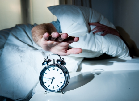 confuse: sleeping man disturbed by alarm clock early morning