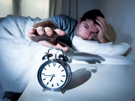 early morning: sleeping man disturbed by alarm clock early morning