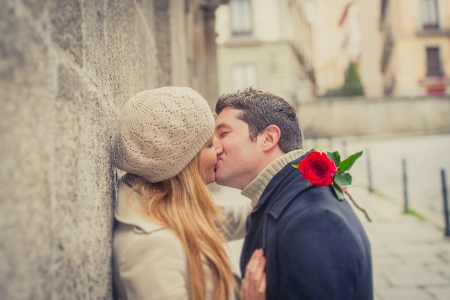 young man giving his girlfriend a rose and kissing celebrating valentines day  photo